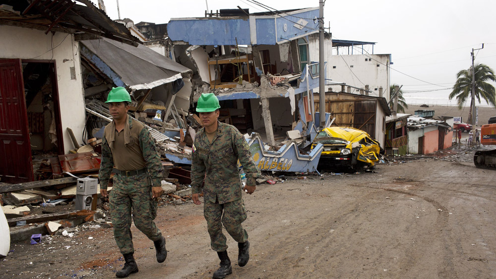Soldiers walk to meet their unit before clearing the streets of debris days after the earthquake in Pedernales, Ecuador, Friday, April 22, 2016. President Rafael Correa said Ecuador's worst earthquake in decades caused billions of dollars of damage and he is raising sales taxes and putting a one-time levy on millionaires to help pay for reconstruction. (AP Photo/Rodrigo Abd)